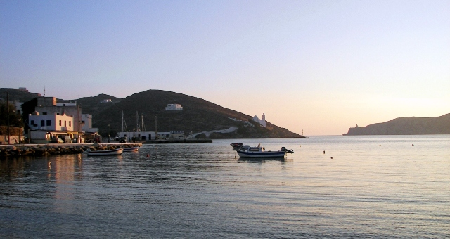 Sunset in Ios' port, calm sea, fishing boat, white buildings, church, ferry routes Cyclades