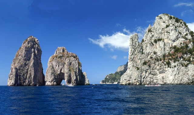 Rocks in the sea, blue sky, beaches of Capri, ferry routes to the Amalfi Coast