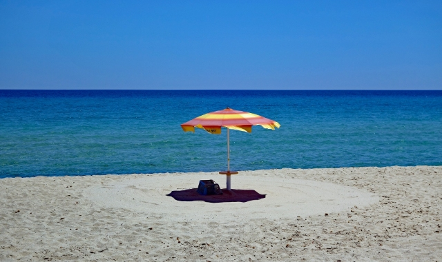 Sea in Sardinia, umbrella, Porto Torres, holidays and ferry tickets from mainland Italy