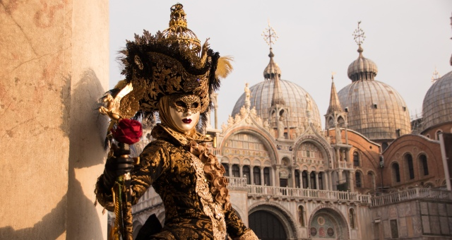 Carnival in Venice, female figure, dress, mask, cathedral, holidays in Italy, ferry tickets