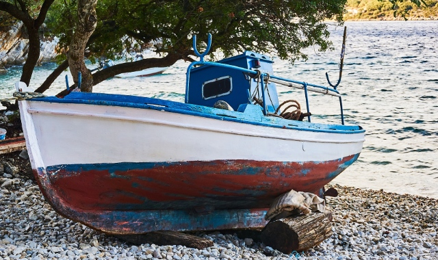 blue, white and red boat on the shore, beach of Ithaca, ferry tickets to the Ionian Sea