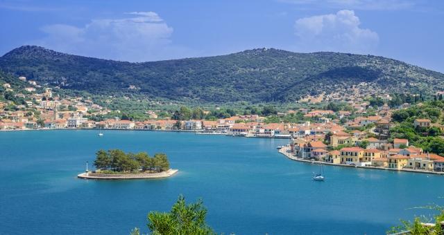 Το λιμάνι της Ιθάκης, ήρεμη θάλασσα, νησί, δέντρα, σπίτια, στέγες, βουνό, μπλε ουρανός, σύννεφα