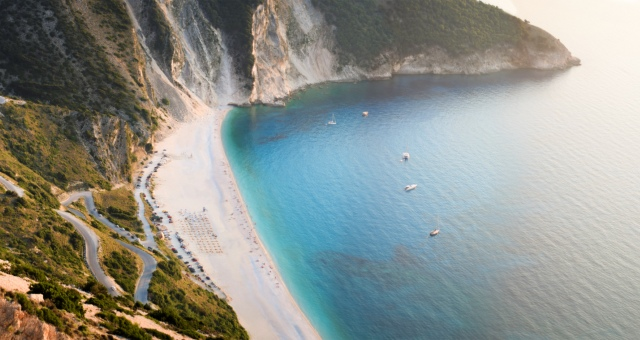 Aerial view of the Myrtos beach in Kefalonia, sandy beach, blue-green waters, holidays in the Ionian sea, ferry tickets