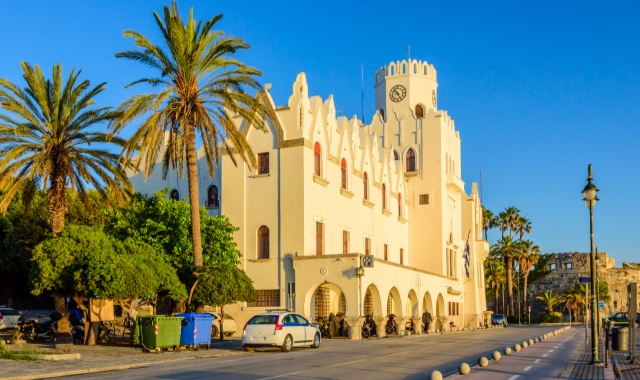 Traditional building in the port of Kos, palm trees, clock, bike path, sunset, castle