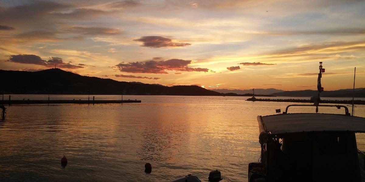 Ηλιοβασίλεμα στο λιμάνι της Κύμης, σκάφος, φάρος, προβλήτα, νησί, θάλασσα