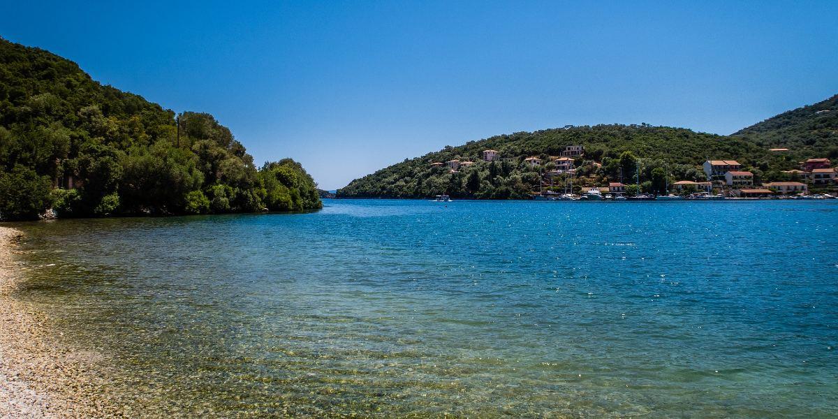 Κρυστάλλινα, γαλάζια νερά, βότσαλα, δέντρα, παραλία Σύβοτα στη Λευκάδα