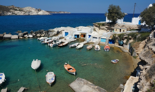 port of Mandrakia in Milos, boats and white houses, blue sea, ferry routes