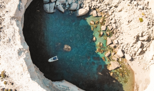 view from above, little gulf in Milos, small white boat, white rocks