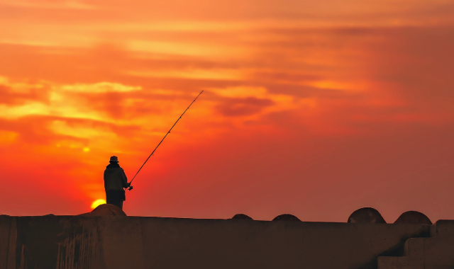 Fisherman fishing in the port of Al Hoceima, Morocco, orange sunset, holidays, ferry routes