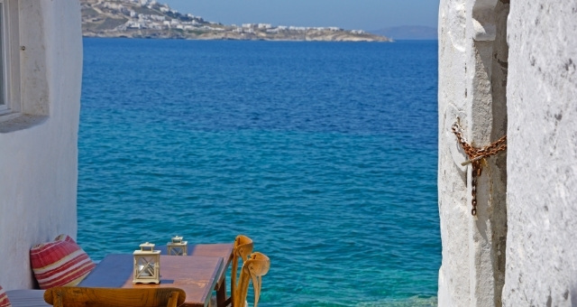 Restaurant tables in Little Venice, old town of Mykonos, sea view