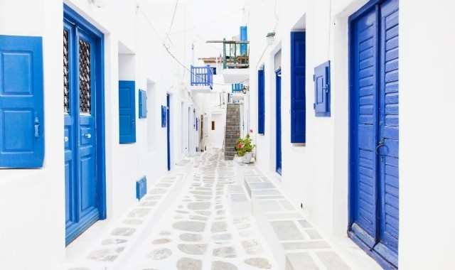Houses with blue windows at an alley in Mykonos
