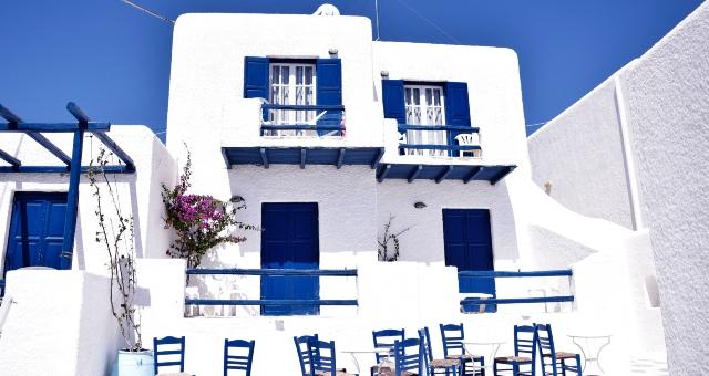 Καφενείο στη Μύκονο, τραπεζάκια και ψάθινες καρέκλες, μπλε και άσπρα σπίτια, παράθυρα, βουκαμβίλια