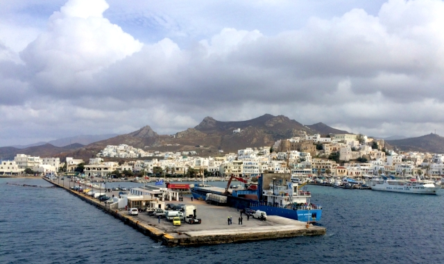 Ferries, people, cars at the port of Naxos, town castle, island, clouds