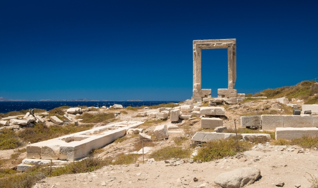 The ruins of the Portara gate in Naxos, sightseeing, blue sky, sea view, port of Naxos, ferry tickets
