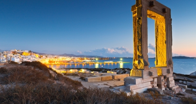 The monument of Portara above the port and city of Naxos, in yellow lighting