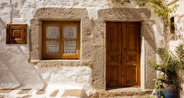 Παραδοσιακό σπίτι στη Χώρα της Πάτμου, ξύλινη πόρτα, κέντημα, κουρτίνα, γλάστρα,
