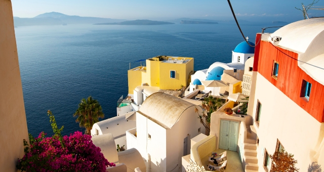 view from Santorini, white houses, blue, orange and yellow details, purple flower, ferry routes to santorini 2020