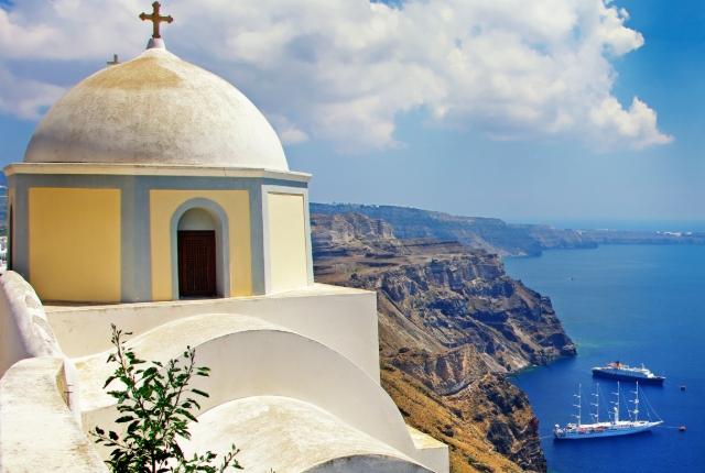 Iglesia blanca y amarilla, borde del acantilado, impresionante vista al mar de Santorini, rutas de ferry a las islas griegas