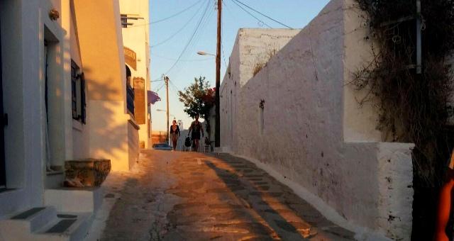 Πλακόστρωτο δρομάκι, Χώρα Σχοινούσας, άνθρωποι, σκιές, άσπρα σπίτια, ήλιος, απόγευμα