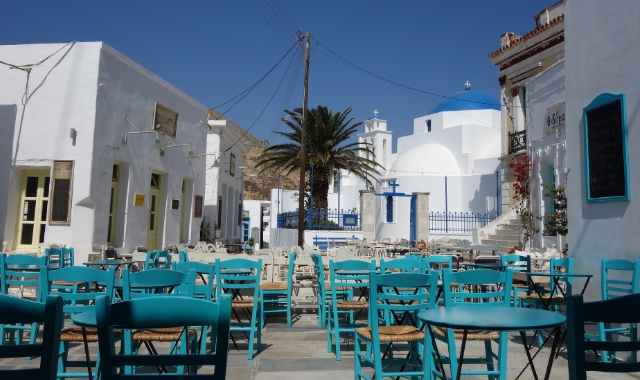 blue chairs and tables, white buildings, palm tree, cafe in Serifos, ferry routes