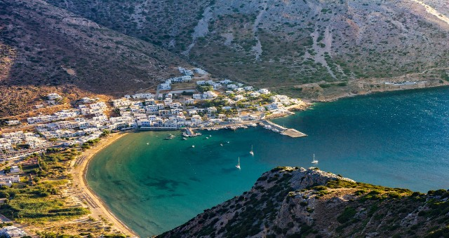 aerial view of the port in Sifnos, sea and mountain, white buildings, ferry tickets