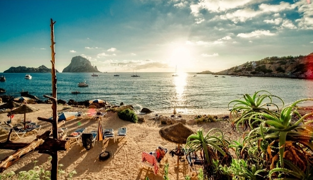 ibiza, bohemian lifestyle, cala d'hort, sun loungers, parasols, sea, boats, sunset, sandy beach