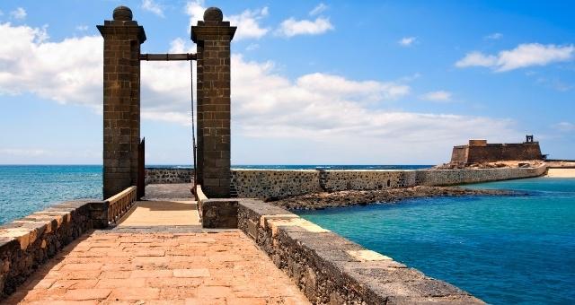 Ein Portal mit zwei Türmen führt über eine Brücke zu einem Schloss auf dem Meer