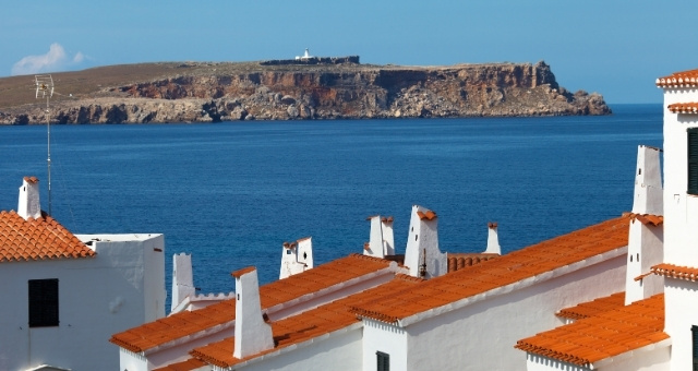 Cape and lighthouse of Cavalleria, Fornells village, blue sea, houses, cliff, Menorca
