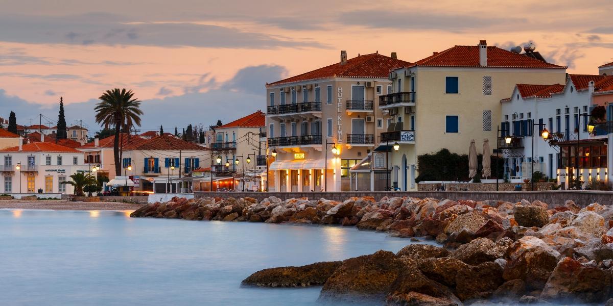 Νεοκλασικά κτήρια στο λιμάνι των Σπετσών, βράχια, φώτα, ηλιοβασίλεμα