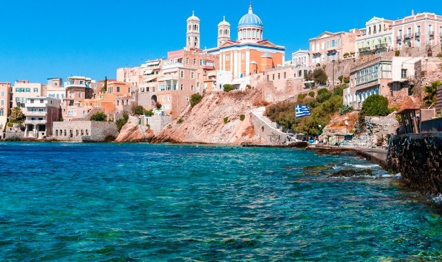 beach with green waters next to Ermoupolis, neoclassical buildings in Syros