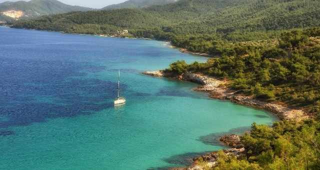 Rocky beach in Thassos with turquoise waters and green coast