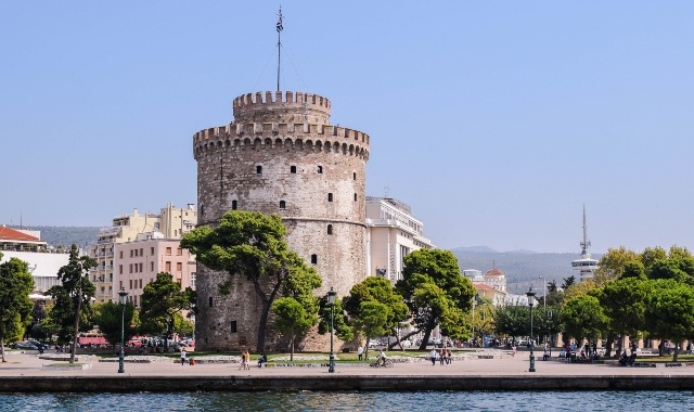 the White Tower of Thessaloniki, green trees, landmark in Greece, ferry routes