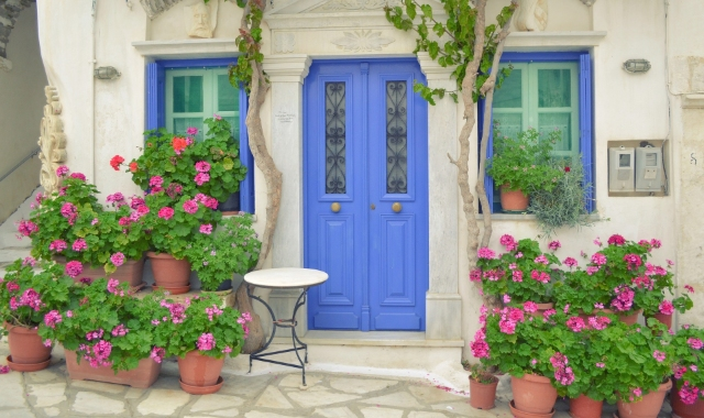 Colourful village in Tinos, traditional architecture, flowers, holidays in the Cyclades, ferry tickets