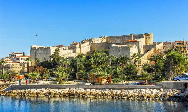 the castle of Cesme, green palm trees, rocks, calm sea, ferry route Cesme-Chios